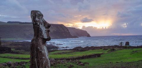 Die Osterinsel zu Sonnenuntergang am Ozean mit Bergen und Moai Statue