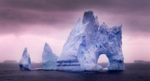 Eisberg in der Antarktis mit rosa Himmel im Hintergrund