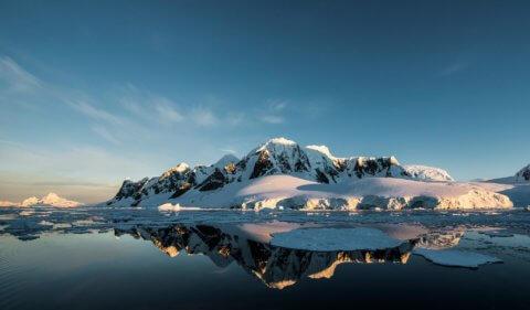 Schneebedeckter Berg vor spiegelglattem Wasser in der Antarktis
