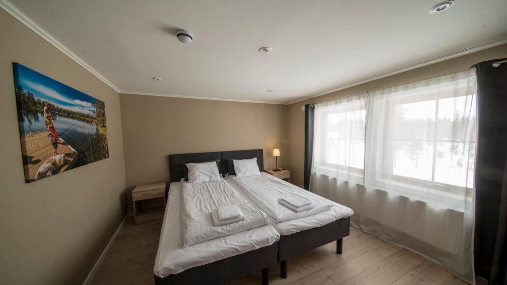 Gästezimmer mit Doppelbett in der Pinetree Lodge Schweden