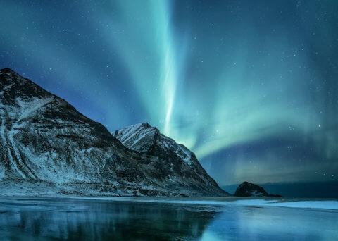 Nordlichter tanzen hinter einem Berg